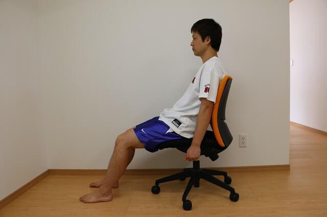 浅く腰かけ、後ろにもたれかかる姿勢